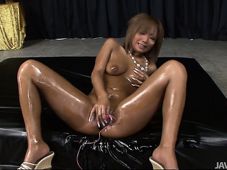 Oiled up asian bimbo with a dark tan fucks herself with many toys