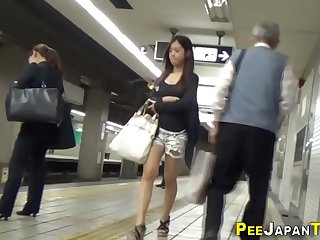 Squatting asians urinate in public toilet